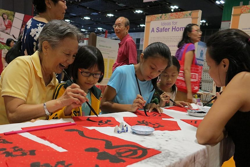 Retiree Madam Ong Beng Kee, 69 (in yellow), and her granddaughter Kristin Lim, 9, trying out Chinese calligraphy at the 50plus Expo at Suntec Convention and Exhibition Centre on Saturday May 16, 2015.-- ST PHOTO: YEO SAM JO