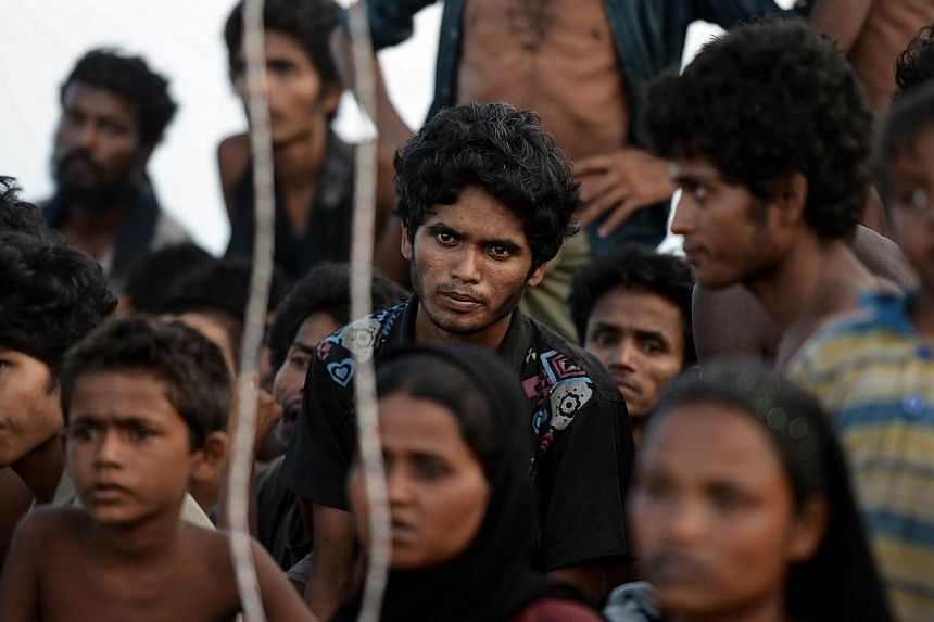 Rohingya migrants sitting in a boat drifting in Thai waters off the southern island of Koh Lipe in the Andaman. Trafficking experts say Thailand is the centre of a multi-million-dollar trade run by competing transnational criminal syndicates. -- PHOT