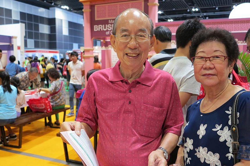 Retirees Gan Siew Lim, 75 (left), and Madam Goh Sai Hea, 70, at the 50plus Expo at Suntec Convention and Exhibition Centre on Saturday, May 16, 2015.Mr Gan said he is interested picking up computer skills.-- ST PHOTO: YEO SAM JO