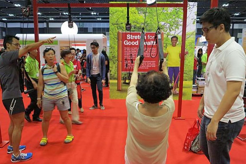 An old lady trying out some exercises at the 50plus Expo at Suntec Convention and Exhibition Centre on Saturday, May 16, 2015.-- ST PHOTO: YEO SAM JO