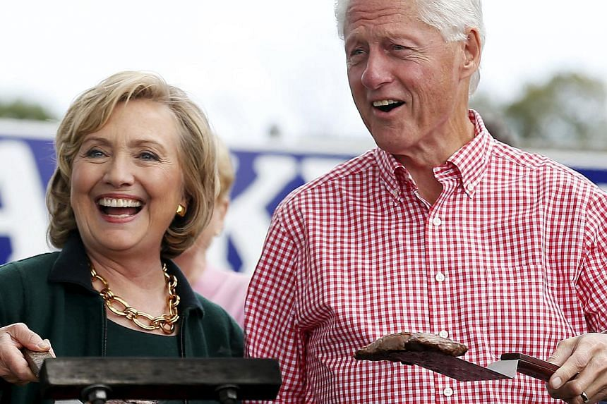 Former US Secretary of State Hillary Clinton and her husband former US President Bill Clinton holding up some steaks at the 37th Harkin Steak Fry in Indianola, Iowa, in this Sept 14, 2014 file photo. The Clintons earned at least US$30 million (S$40 m