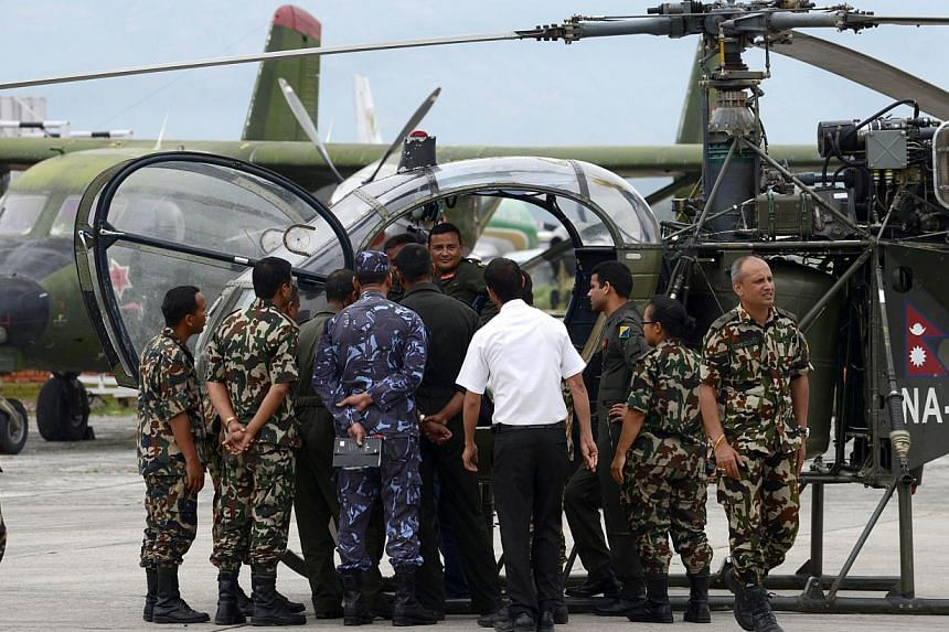 Nepalese army personel gathering in front of a helicopter, whose crew spotted the wreckage of a US Marine helicopter, at the army air base in Kathmandu on May 15, 2015 -- PHOTO: AFP