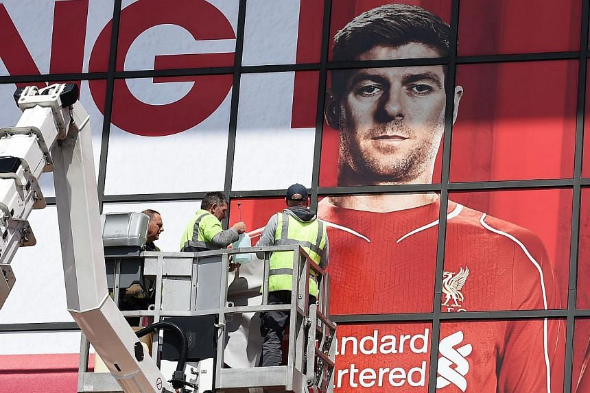 Workers pasting a poster over Liverpool's English midfielder Steven Gerrard as they replace sections of a mural outside The Kop stand at Anfield, Liverpool, north-west England on May 13, 2015. -- PHOTO: AFP