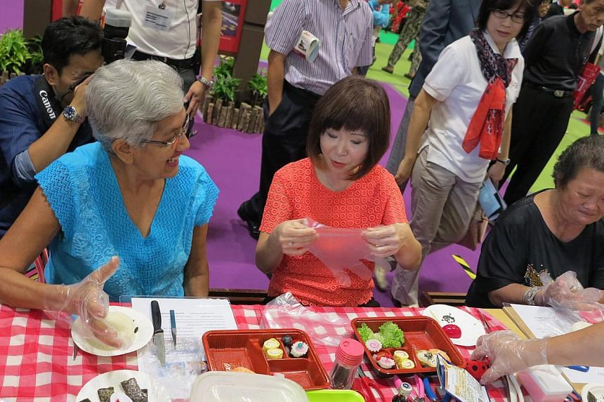 Senior Minister of State for Health, Dr Amy Khor (in pink), learning how to make sushi with some seniors at the 50plus Expo event at Suntec Convention and Exhibition Centre on Saturday, May 16, 2015.-- ST PHOTO: YEO SAM JO