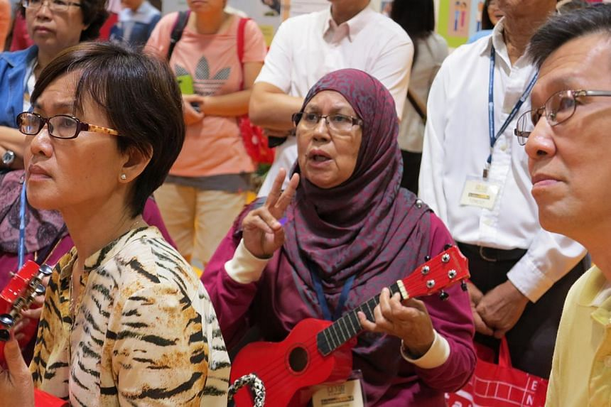 Retired teacher, Madam Kasummah Salleh, 65, (in purple), strumming the ukulele for the first time at the 50plus Expo event at Suntec Convention and Exhibition Centre on Saturday, May 16, 2015. She bought a ukulele after this crash course.