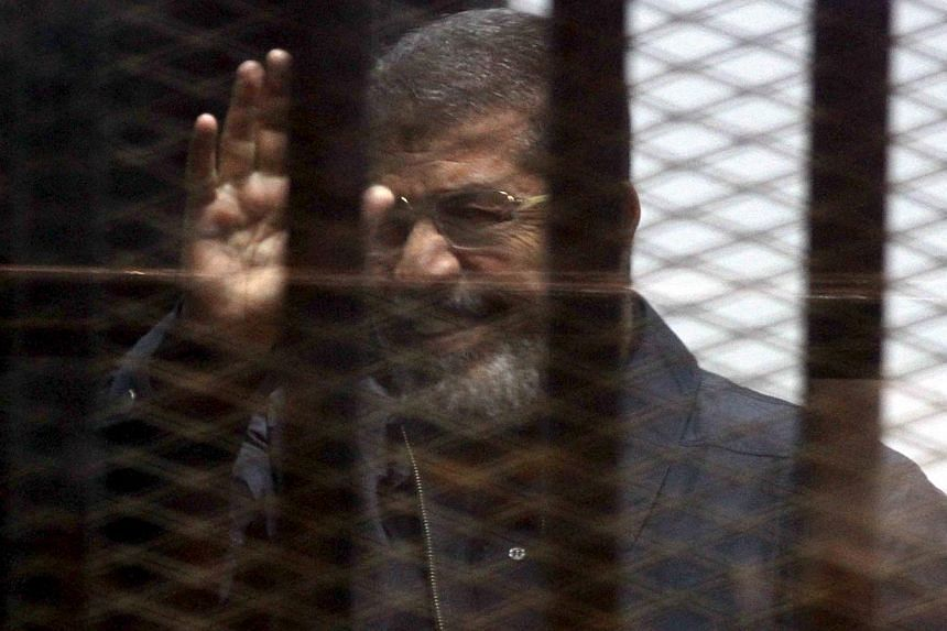 Ousted Egyptian president Mohamed Mursi is seen behind bars during his trial at a court in Cairo on April 30, 2015. -- PHOTO: REUTERS
