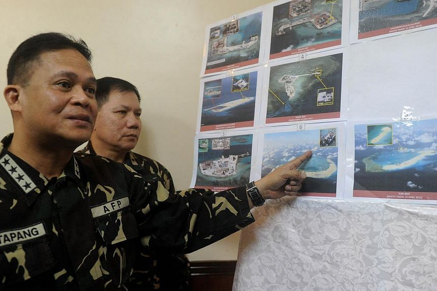 Filipino military chief Gregorio Catapang pointing to aerial photos of Chinese construction over reefs and shoals in the Spratly archipelago during a press briefing in Manila last month. The Philippines has expressed alarm about China's reclamation a