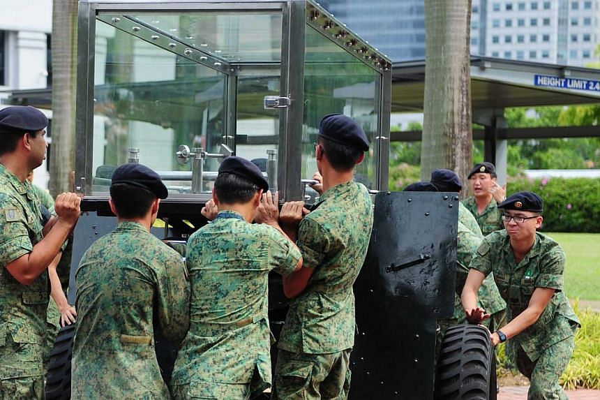 (Above) SAF personnel rehearsing with a ceremonial gun carriage bearing a glass case for the casket a day after the death of Mr Lee Kuan Yew. (Below, in white) Chief of Defence Force Lieutenant-General Ng Chee Meng at a rehearsal at the University Cu