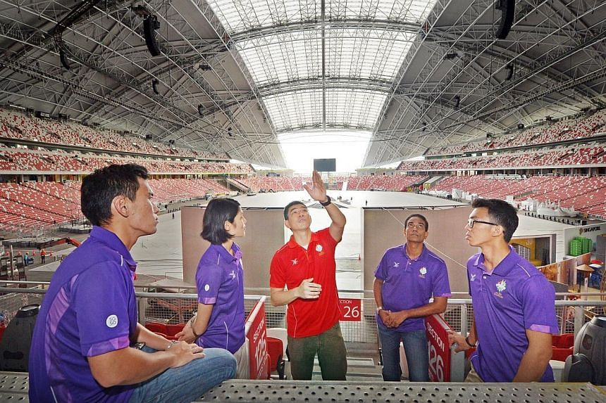 Chief Artillery Officer Lawrence Lim (centre) having a discussion with (from left) Captain Ang Wee Kiong, 26, Captain Hong Ruoyi, 26, First Warrant Officer Nedunsezhian, 48, and Lieutenant Demerin Allen Christian Gadon, 21, at the National Stadium on