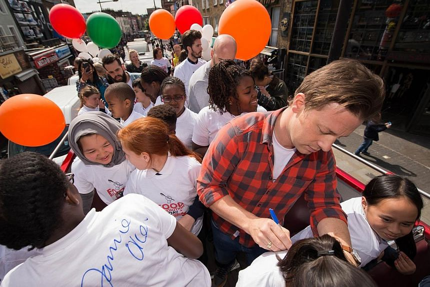 British chef and television presenter Jamie Oliver signs a child's shirt during an open-top bus tour of central London to promote Food Revolution Day on May 15, 2015. Jamie Oliver is calling for a global campaign to put compulsory practical food educ