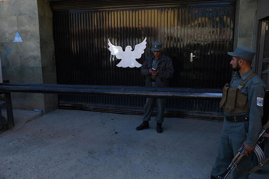 Afghan policemen stand guard at the entrance of the Park Palace guesthouse in Kabul on May 14, 2015. -- PHOTO: AFP