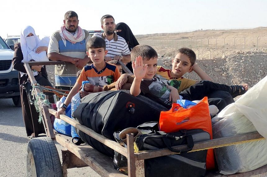 Sunni people react as they flee the violence in the city of Ramadi. Islamic State militants raised their black flag over the local government headquarters on May 15, 2015 and claimed victory through mosque loudspeakers after overrunning most of the w