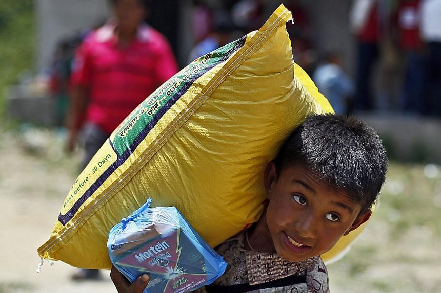 A Nepalese earthquake survivor carries a sack of rice during a food distribution in Jaharsingh Pauwa, Nepal on May 16, 2015. -- PHOTO: EPA