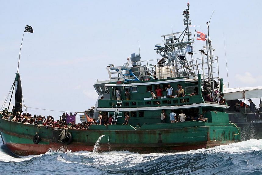 A boat with migrants is being towed away from Thailand by a Thai navy vessel, in waters near Koh Lipe island on May 16, 2015. -- PHOTO: REUTERS
