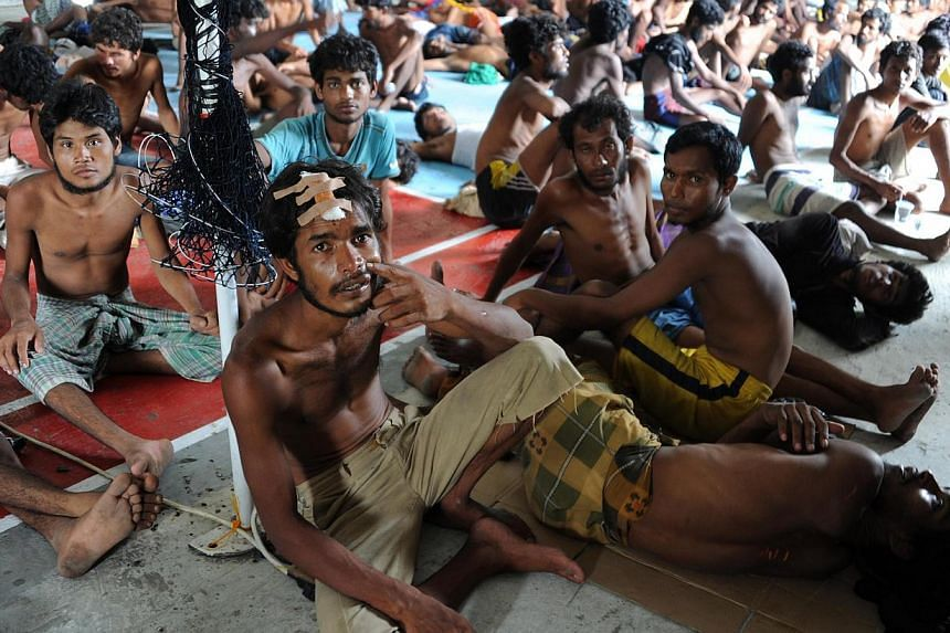 A group of rescued migrants, mostly Rohingya from Myanmar and Bangladesh, sit upon their arrival at the new confinement area in the fishing town of Kuala Langsa in Aceh province on May 15, 2015. -- PHOTO: AFP