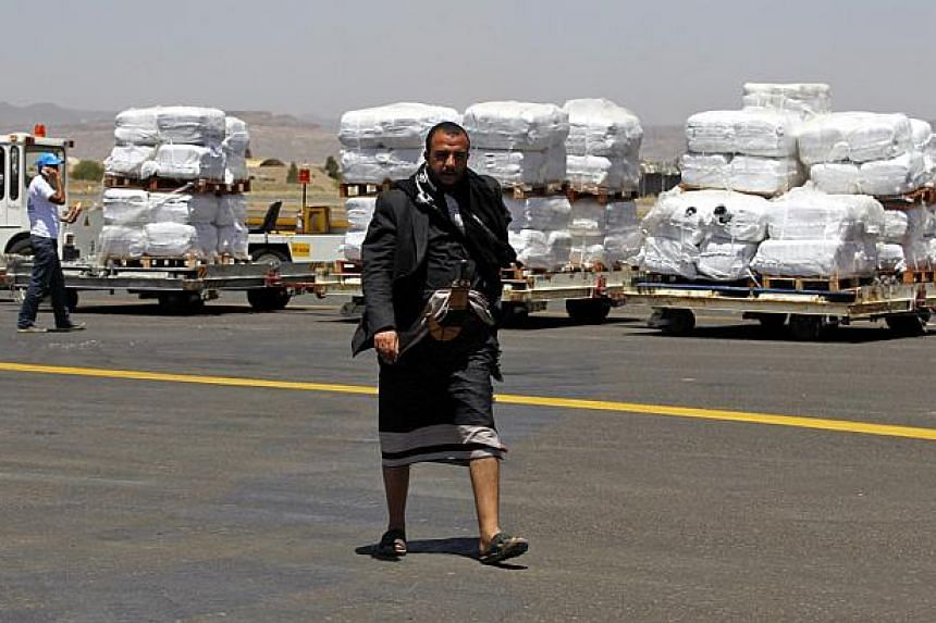 A Yemeni walks in front of emergency aid supplied by the United Nations High Commission for Refugees after it was unloaded at Sana'a International Airport, in Sana'a, Yemen, on May 16, 2015. -- PHOTO: EPA