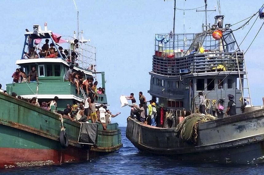 Ethnic Muslim Rohingya migrants, believed to have come from Myanmar and Bangladesh (left), receive aid supplies from a Thai fishing boat in the Andaman Sea close to Malaysia and southern Thailand on May 14,2015. Malaysia's foreign minister urge