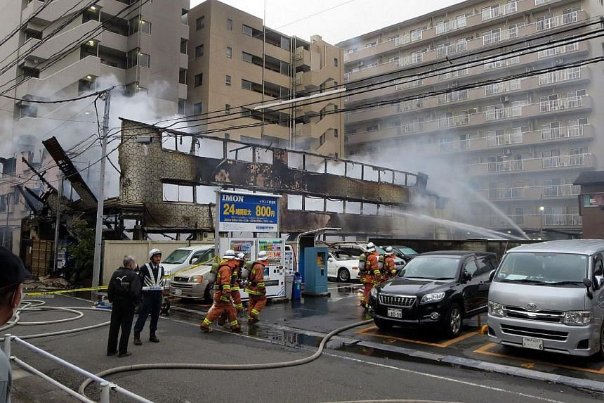 Firefighters spray water on a day-laborer's lodging house in Kawasaki, Kanagawa prefecture in suburban Tokyo on May 17, 2015. At least four people were killed in a fire early Sunday at two adjacent hostels in Kawasaki, south-west of Tokyo, while 19 o
