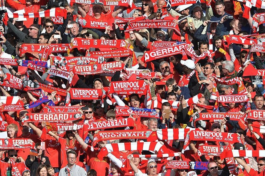 Liverpool fans shows their support for departing captain Steven Gerrard by waving scarfs before the English Premier League football between Liverpool and Crystal Palace at Anfield on May 16, 2015. -- PHOTO: EPA