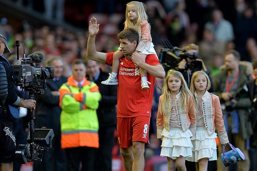 Liverpool captain Steven Gerrard with his three daughters at Anfield. -- PHOTO: EPA