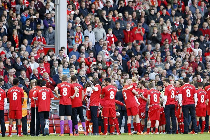 Liverpool players wear Gerrard shirts as they wait for their departing captain to be presented on the pitch after his final game at Anfield. -- PHOTO: REUTERS