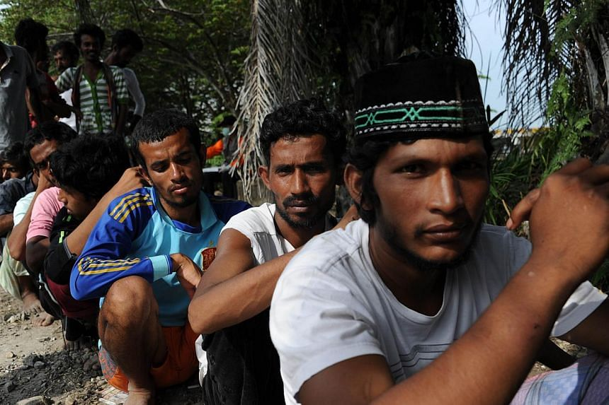 In this photograph taken on May 16, 2015, a group of rescued migrants from Bangladesh line up to be documented by Indonesian immigration personnel at the confinement area in the fishing port of Kuala Langsa in Aceh province where hundreds of migrants