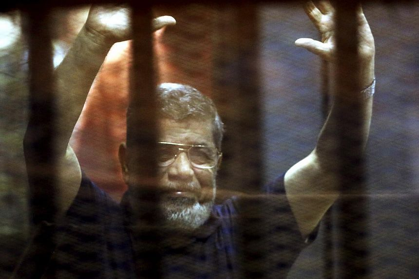 Former Egyptian President Mohamed Mursi reacts behind bars with other Muslim Brotherhood members at a court in the outskirts of Cairo, Egypt on May 16, 2015. -- PHOTO: REUTERS