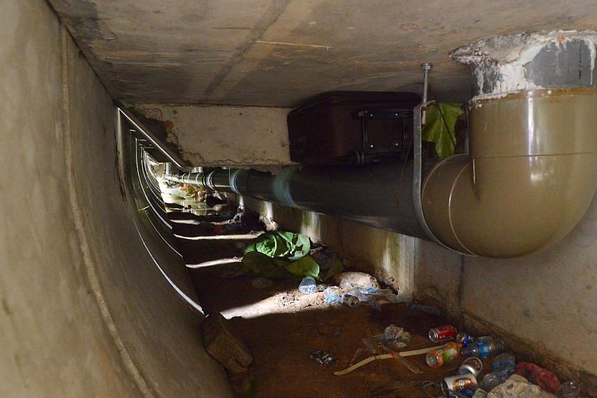 (Right) A wedged stone holding what appears to be a clothes line. (Below) One of the two inconspicuous openings to the hideout along Nicoll Highway. Food waste, empty water bottles and beer cans (above) litter the hideout under Merdeka Bridge, where