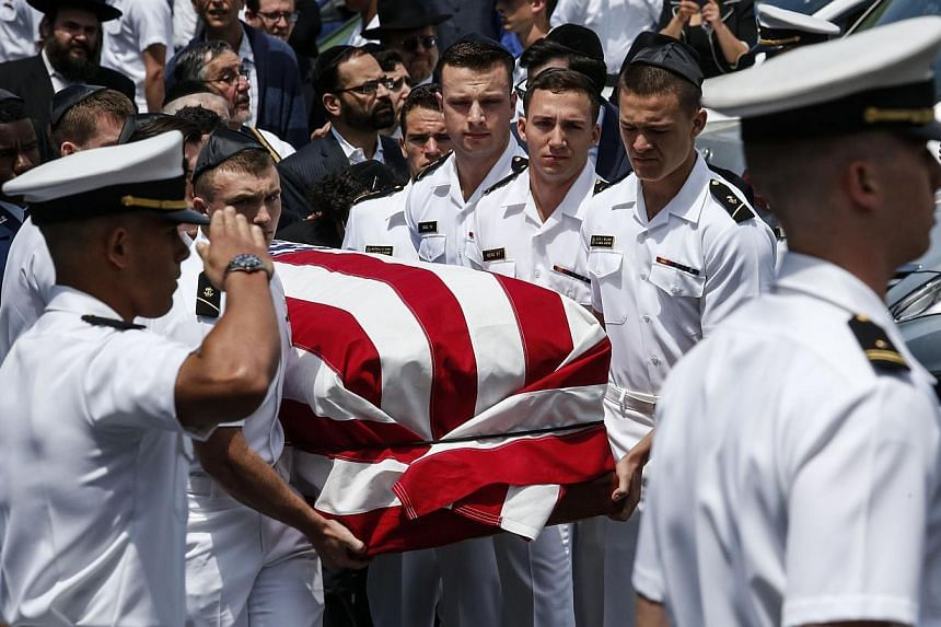 Midshipmen from the US Naval academy carry Midshipman Justin Zemser to a waiting car after his funeral on May 15, 2015 in Hewlett, New York. Zemser was one of eight people killed in the derailment of an Amtrak train on May 12th in Philadelphia. -- PH