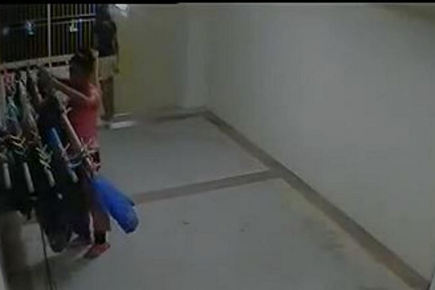 A screengrab of CCTV footage showing one girl allegedly stealing from a clothes rack at a Housing Board corridor while another girl acts as a lookout. -- FACEBOOK/ALLSGSTUFF