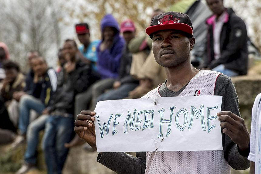 """A migrant holds a sign reading """"We need a home"""" during a visit by the French interior minister to their shelter in Calais, northern France, on May 4, 2015. -- PHOTO: AFP"""