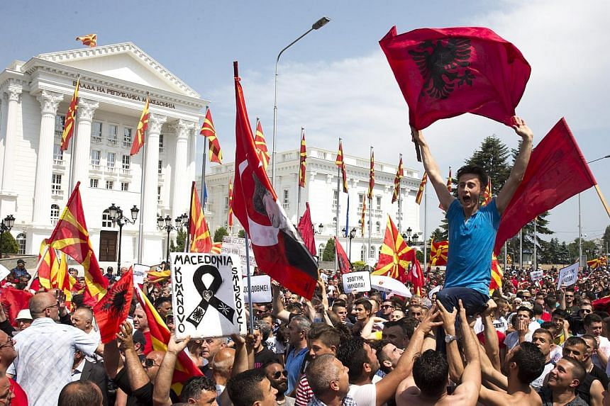 Protestors wave Macedonian and Albanian flags during a rally in front of the Government Building in Skopje, The Former Yugoslav Republic of Macedonia, on May 17, 2015. More than 20,000 people rallied in Macedonia's capital on Sunday to demand th