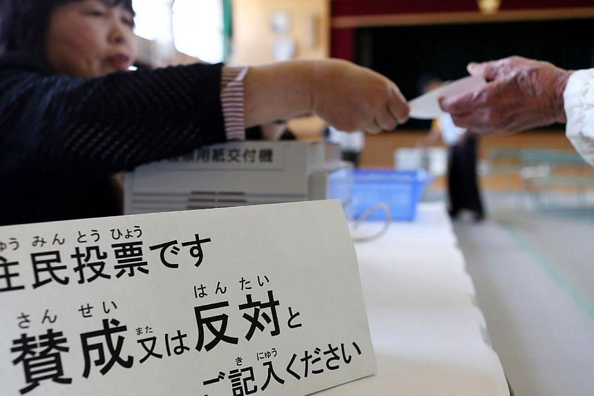 A resident (right) receives a ballot at a polling station in Osaka on May 17, 2015 to vote on a referendum to reform the city administration into a metropolitan government.The people of Japan's second city Osaka narrowly voted down Sunday a pla