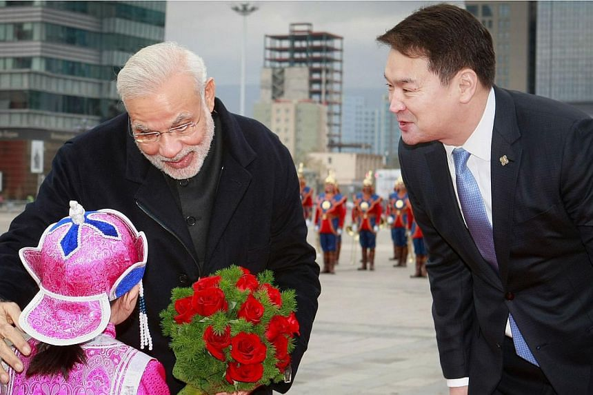 Mongolian Prime Minister Chimed Saikhanbileg (right) looks on as India's Prime Minister Narendra Modi receives a bouquet of flowers from a Mongolian child during a welcoming ceremony at the Chinggis Square in Ulan Bator on May 17, 2015. MrModi