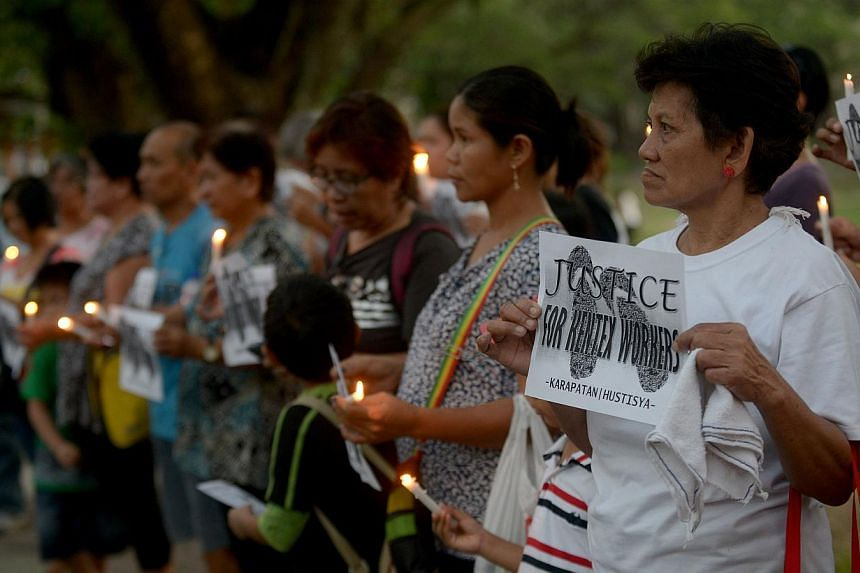 Activists hold candles and placards during a rally in Manila on May 16, 2015 for the victims of a fire that gutted a footwear factory on May 13.Philippine officials called on Sunday, May 17, for criminal penalties for factory owners who violate