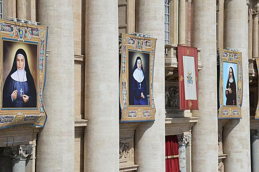 A picture shows tapestries of four blessed nuns (from left) St Marie-Alphonsine Danil Ghattas, St Emilie de Villeneuve, St Maria Cristina of the Immaculate Conception and St Maryam Baouardyon the facade of St Peter's basilica during a papal mas