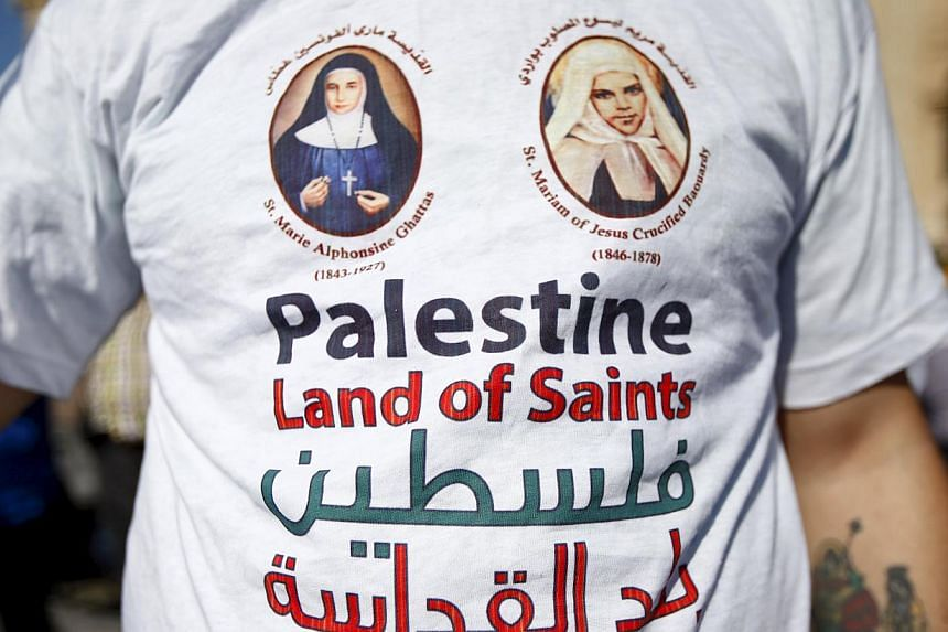 A member of the faithful wears a T-shirt with the picture of the two Palestinian nuns being canonised before Pope Francis led a ceremony for the canonisation of four nuns at St Peter's square in the Vatican City, on May 17, 2015. -- PHOTO: REUTERS&nb