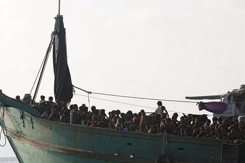 Migrants are seen aboard a boat tethered to a Thai navy vessel, in waters near Koh Lipe island, on May 16, 2015.-- PHOTO: REUTERS