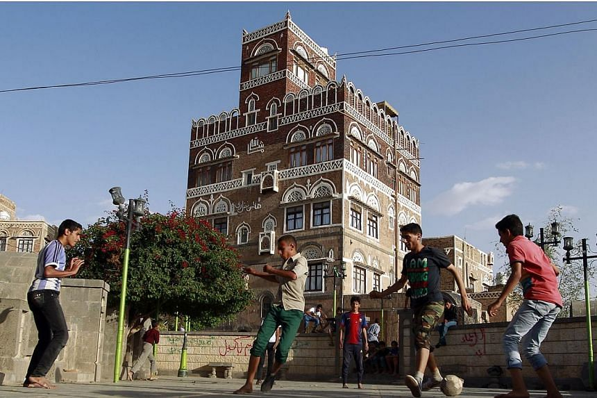 Yemenis play football on a street in Sanaa's old city on May 14, 2015.The United Nations envoy to Yemen, Ismail Ould Cheikh Ahmed, called on a Saudi-led military coalition and the country's warring parties to extend by five more days a ceasefir
