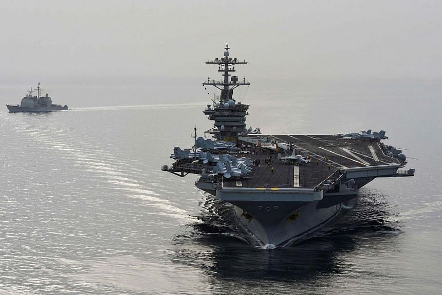 American aircraft carrier USS Theodore Roosevelt and guided-missile cruiser USS Normandy sail in the Gulf on April 16, 2015, supporting strike operations in Iraq and Syria as directed.At least 32 Islamic State in Iraq and Syria (ISIS) members,