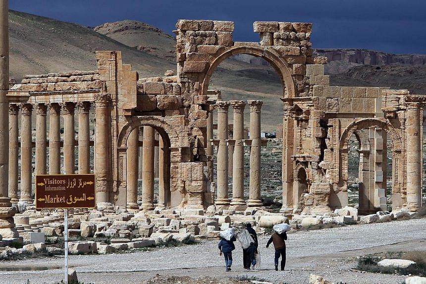 A file picture taken in March 2014 shows Syrian citizens walking in the ancient oasis city of Palmyra, 215km north-east of Damascus. -- PHOTO: AFP