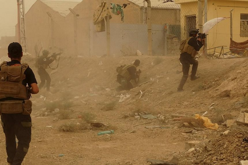 Iraqi security forces defend their headquarters against attacks by ISIS extremists in the eastern part of Ramadi in Anbar province on Thursday. ISIS militants raised their black flag over the provincial government compound in the city of Ramadi in we