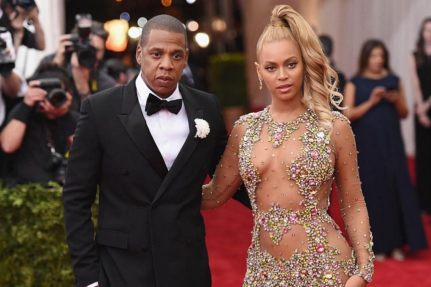 Jay Z (left) with wife and pop star Beyonce at the Met Gala in New York on May 4, 2015. The rap mogul has been quietly using his wealth to post bail for people arrested in protests across the US, said an author close to him. -- PHOTO: AFP