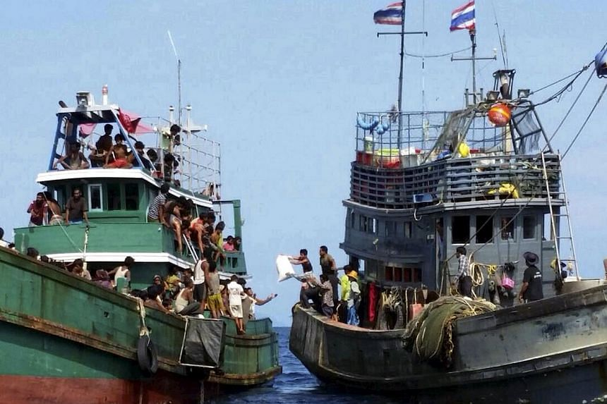 Thai fishermen (right) give some supplies to migrants on a boat drifting 17km off the coast of the southern island of Koh Lipe, Thailand, on May 14, 2015. -- PHOTO: REUTERS