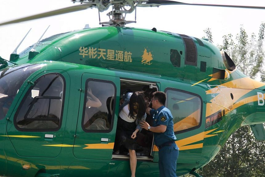 Customers getting out of a helicopter in Beijing during a trial service jointly launched by Chinese general aviation operator Reignwood Star and China's biggest taxi hailing platform on May 15, 2015. -- PHOTO: REUTERS