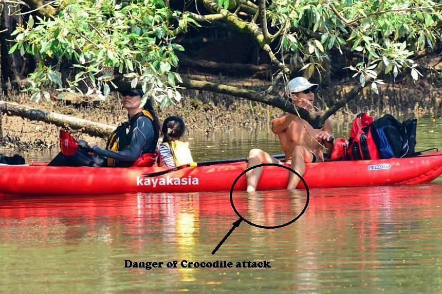 "The man was spotted by Mr Ben Lee having a picnic on the kayak and dangling his legs in the water. The words ""Danger of crocodile attack"" and the circle around the man's legs were added by Mr Lee. -- PHOTO: BEN LEE"