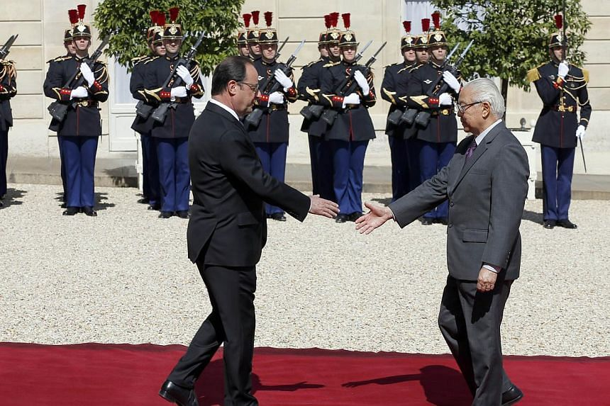 Singapore's President Tony Tan Keng Yam (right) shakes hands with French President Francois Hollande at the Elysee Palace in Paris on May 18, 2015. -- PHOTO: AFP