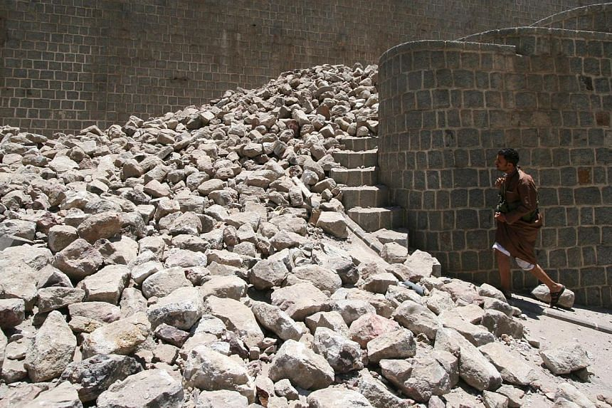 A Houthi militant walks by rubble of a part of the Qahira fort following air strikes in Yemen's south-western city of Taiz on May 12, 2015. -- PHOTO: REUTERS