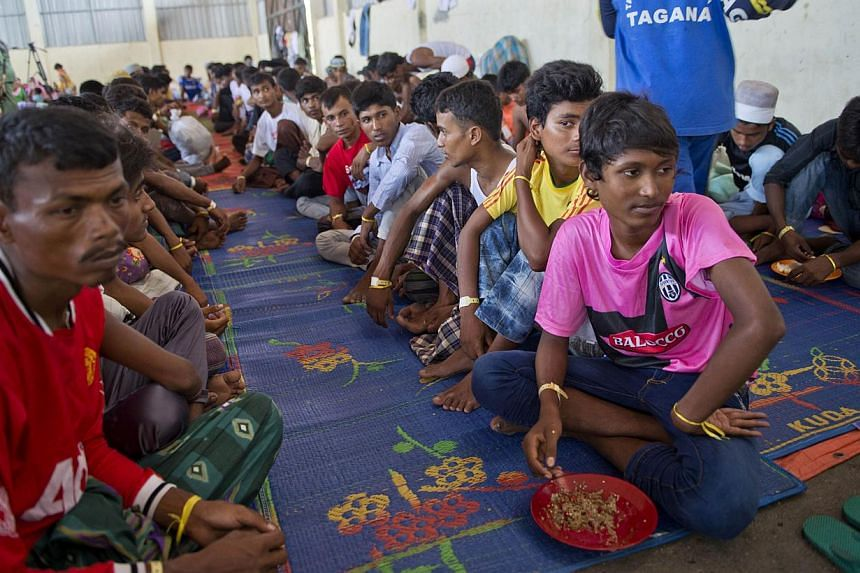 "Rohingya migrants from Myanmar wait for their meal from Indonesian volunteers at the confinement area in the fishing port of Kuala Langsa in Aceh province on May 18, 2015. Myanmar acknowledged on Monday that the international community had ""concern"