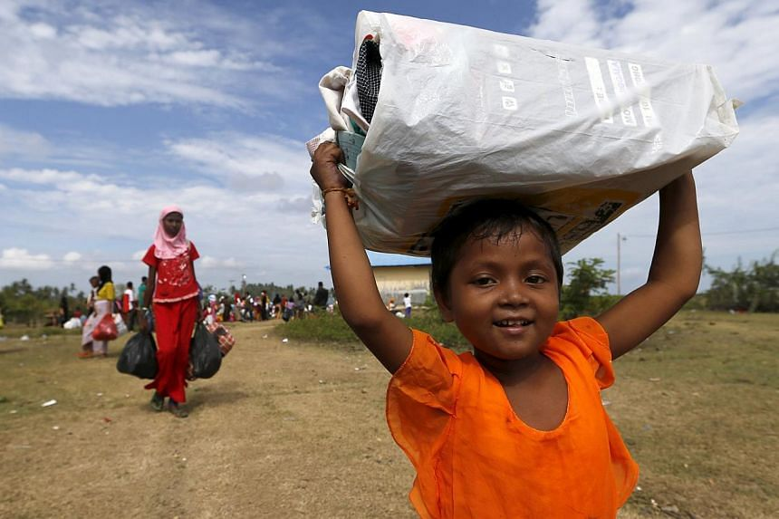 A Rohingya migrant child, who arrived in Indonesia by boat, carrying belongings while walking to a bigger shelter inside a temporary compound for refugees in Kuala Cangkoi village in Lhoksukon, Indonesia's Aceh province, on May 18, 2015. -- PHOTO: RE